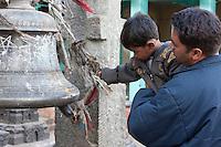 Kathmandu, Nepal.  Nepali Father and Son Ring a Bell at Swayambhunath Temple.  Bells drive evil spirits away.