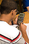 Education High School Mathematics class male student using calculator seen from behind vertical