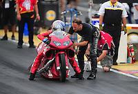 May 13, 2011; Commerce, GA, USA: NHRA pro stock motorcycle rider Angie Smith being helped by husband Matt Smith during qualifying for the Southern Nationals at Atlanta Dragway. Mandatory Credit: Mark J. Rebilas-