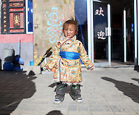A young Tibetan child in a town on the Tibetan Plateau, in western China. Up to 100,000 nomads have been removed from the highland grasslands of the Tibetan Plateau. Climate change, mining and government policy are causing the rapid disappearance of this unique culture.