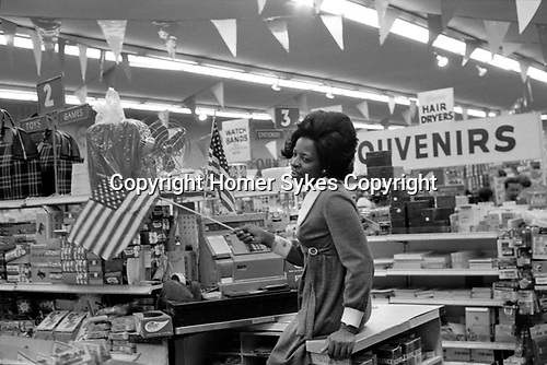African American young woman waving the Stars and Stripes flag she is working in a down town Manhattan New York department store 1972. 1970s USA