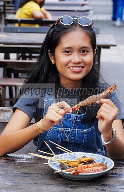 """Asie/Singapour/Singapour: Jeune fille dégustant des brochettes """"Satays"""" et leur sauce"""