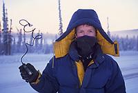 Photographer holds a camera remote cord, frozen stiff in minus 40 below zero, Fairbanks, Alaska.