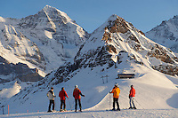 skiers in the winter snow at Mannlichen with the Eiger and Jungfrau mountains behind - Swiss Al;ps - Switzerland