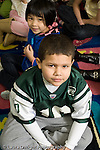 Education Elementary Grade 2 portrait of boy serious female student behind him on rug vertical