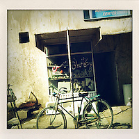 A bicycle propped up outside a plumber's shop in kabul.