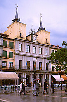 Spain, Segovia. Parishioners after mass shelter under umbrellas as they walk through the Plaza Mayor past the town hall. Segovia Castilla Y Leon Spain.