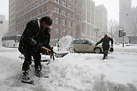 Montreal, March 2nd 2007....An employee shovel snow in front of the Bank of Montreal  on Saint-Jacques street, while a..Snow storm hits Montreal......Photo by Pierre Roussel - Images Distribution