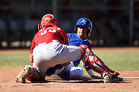 Kansas City Royals shortstop Ricky Aracena (2) slides into catcher Mitch Trees (33) at home plate during an Instructional League game against the Cincinnati Reds on October 14, 2014 at Goodyear Training Facility in Goodyear, Arizona.  (Mike Janes/Four Seam Images)
