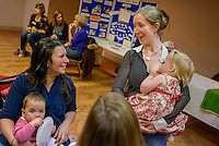 """A mother breastfeeding her toddler while talking to other mothers at a conference.<br /> <br /> Image from the breastfeeding collection of the """"We Do It In Public"""" documentary photography picture library project: <br />  www.breastfeedinginpublic.co.uk<br /> <br /> <br /> Middlesex, England, UK<br /> 2016<br /> <br /> © Paul Carter / wdiip.co.uk"""