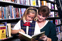 Young girl age 9 reading a book with mother in library or bookstore as she learn