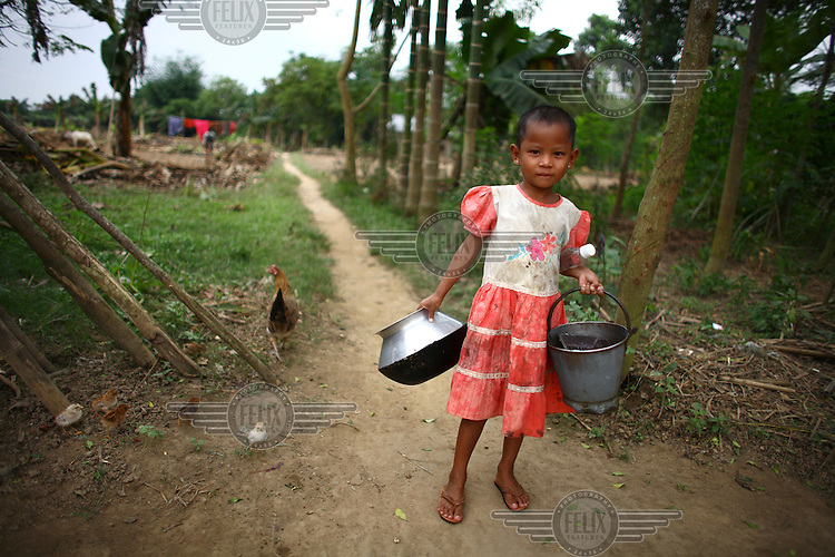 A Garo girl carrying a bucket and a pot. The Garo (or Mandi, as they refer to themselves) are an ethnic minority thought to be of Tibeto-Burmese origin. Prior to British rule they were mostly anamists but missionary work led the majority to convert to Christianity. The Garo of the Madhupur forest have long been under the threat of eviction by the government and the forest that they gain much of their livelihood from is being rapidly destroyed by unregulated logging.