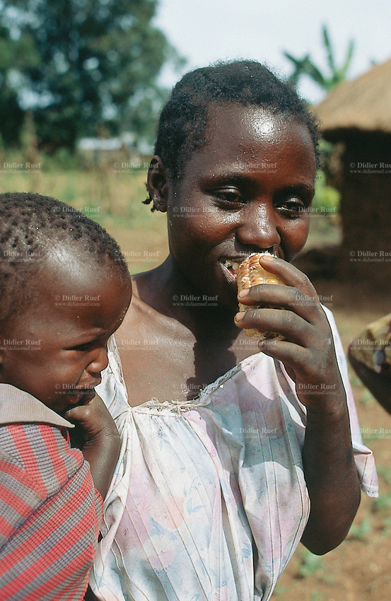 Kenya. Rift Valley Province. Matisi. A woman carries her child in her arms and eats a cob of corn. © 2004 Didier Ruef