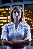 Blonde woman looking at camera with window and lights of Manhattan behind her