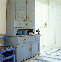 The huge blue-painted dresser in the kitchen was custom made by Swedish carpenters and like the chair next to it has been distressed to look antique