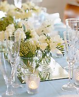 Scented cut flowers on a mirrored tile decorated with little drops of glass add a touch of freshness to a laid table