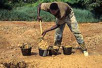 Filling buckets for diamond sifters, Tortiya, Ivory Coast.
