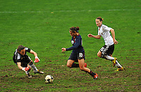 USA midfielder Carli Lloyd tries to beat German goalkeeper Nadine Angerer to the ball.  The USA captured the 2010 Algarve Cup title by defeating Germany 3-2, at Estadio Algarve on March 3, 2010.