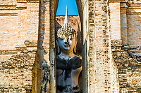 Phra Achana, the Buddha who is not frightened, visible between the brick walls of Wat Si Chum temple in Sukhothai Historical Park, Thailand