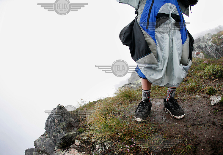 A BASE jumper in sneakers waits for the weather to improve. World BASE Race held in Innfjorden, Norway, where BASE jumpers in wingsuits compete in flying down the mountain. The winner is called the World's Fastest Flying Human Being..©Fredrik Naumann/Felix Features.