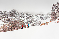 Two climbers approach below the north face of Ben Nevis with the Tower Ridge behind them, Scotland.