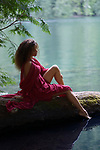 Tranquil romantic portrait on a beautiful young woman sitting on a tree trunk in summer nature scenery with thoughtful expression dipping her foot in calm blue water of a lake Image © MaximImages, License at https://www.maximimages.com