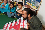 Education preschool 3-4 year olds circle time male teacher going over job chart with children horizontal