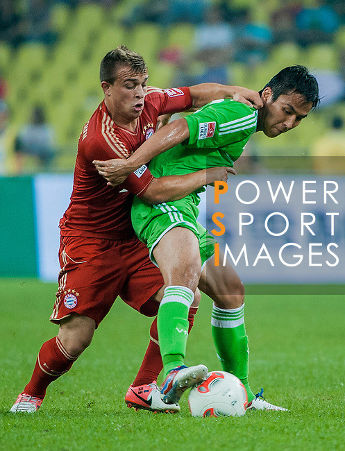 Xherdan Shaqiri of Bayern Munich and Makoto Hasebe of VfL Wolfsburg in action during a friendly match as part of the Audi Football Summit 2012 on July 26, 2012 at the Guangdong Olympic Sports Center in Guangzhou, China. Photo by Victor Fraile / The Power of Sport Images