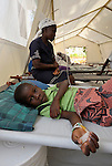Paul Biberstend, 6, is treated for cholera in treatment center run by Oganizasyon Sante Popilè (OSAPO) Montrouis, Haiti. Cholera appeared on the quake-ravaged Caribbean island nation in late 2010. OSAPO's work is supported by Diakonie Katastrophenhilfe and the Lutheran World Federation, both members of the ACT Alliance. In addition to treating people infected with cholera, OSAPO sends teams of health educators into urban and rural communities to provide education, distribute anti-bacterial soap and oral rehydration salts, and refer sick patients back to the OSAPO clinic. Behind the patient is his mother, Odette...