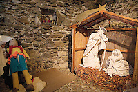 """Switzerland. Canton Tessin. Vira Gambarogno. The old town shows an exhibit of various Nativity scenes, illuminated at night for the Christmas holiday season. A Nativity Scene, may be used to describe any depiction of the Nativity of Jesus in art, but in the sense covered here, also called a crib or in North America and France a crèche (meaning """"crib"""" or """"manger"""" in French). It means a three-dimensional folk art depiction of the birth or birthplace of Jesus, either sculpted or using two-dimensional (cut-out) figures arranged in a three-dimensional setting. Christian nativity scenes, in two dimensions (drawings, paintings, icons, etc.) or three (sculpture or other three-dimensional crafts), usually show Jesus in a manger, Joseph and Mary in a barn (or cave). Stone walland a puppet.  © 2007 Didier Ruef"""