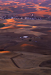 The sun casts orange and pink light during a colorful sunrise across the Palouse farmland of Eastern Washington State.