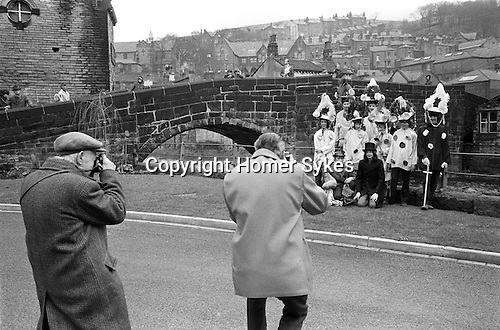 """Midgley Pace Egg Play Hebden Bridge, Yorkshire. England. 1970s. Children of Calder Valley High School who annually perform the traditional Easter Pace Egg Mumming play. 1972.<br /> <br /> There are several theories to the word 'Pace', it is possibly derived from the Latin pascha, literally meaning Easter, or the Hebrew word for Passover. Or alternatively it may simply be a dialect form of the word """"peace"""".<br /> The Pace Egg Play is a traditional village Mumming play that some researchers believe can be traced back to Celtic, Egyptian and Syrian traditions. However the first recorded text of a play of this type is as late as 1738. It is unusual for the play to be performed at Easter, as it is in West Yorkshire. In most parts of England the plays are performed during Christmas, New Year or on All Souls Day in November. The play is nearly always performed by men and boys, at various out door locations around their community.<br /> Passed down over generations the Pace Egg Play has changed, but central to all variations of the play are the hero and villain usually St George and the Black Prince, who take part in a fight one of whom is subsequently wounded or killed. A Doctor is then called for and he resurrects the fallen hero. This it is believed symbolises the emergence of Spring and its victory in battle over Winter.  The plays characters today differ slightly from region to region. In the Midgley version the characters are, a Fool, St George, Bold Slasher, Doctor, Black Prince, King of Egypt, Hector, Toss Pot and the Bugler, and is performed by school boys from Calder Valley High School at Midgley. Their costumes include strange headgear comprising a towering edifice garlanded with paper flowers. The Midgley play was revived in 1932 thanks to the local journalist and historian Henry Harwood."""