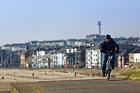 Pictured: A man cycles at Swansea seafront in Wales, UK. Friday 23 February 2018<br /> Re: Parts of the UK have been enjoying sunshine with freezing cold temperatures.