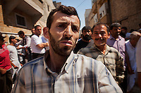 A family member reacts as Free Syrian Army (FSA) fighters and civilians search for bodies and clear rubble from a residential home destroyed by two missiles fired from Syrian Airforce fighter jets that were targeting the neighbouring FSA headquarters in Aleppo. Eleven civilians from two families died including at least four children.