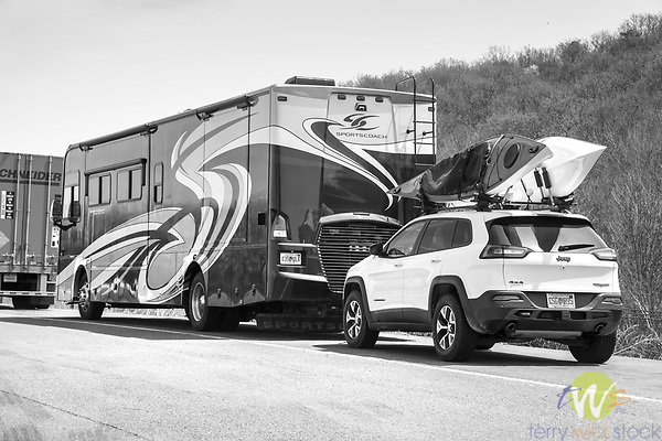 Large motor home with suv and kayaks.