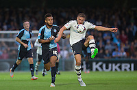 Shaun Hutchinson of Fulham clears the ball under pressure from Aaron Amadi Holloway of Wycombe Wanderers during the Capital One Cup match between Wycombe Wanderers and Fulham at Adams Park, High Wycombe, England on 11 August 2015. Photo by Andy Rowland.