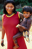 A-Ukre Village, Brazil. Kayapo woman, Kam Ton holding her son and eating a fruit. Xingu park.