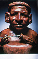 World Civilization:  Moche Culture--Man taking coca in same way modern natives of the Andes do. Having placed quid of coca in cheek, takes powdered lime from gourd, which cuts bitterness and releases small amount of cocaine. Part of a stirrup spout bottle.