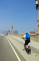 Holland climbs the 1st Street Bridge on his Yedoo Dragstr kick scooter during the during the 2017 (17th annual) Los Angeles River Ride.  The LA skyline is just creeping into view over the top of the bridge.