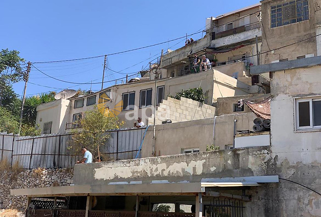 Israeli forces demolish a Palestinian building in the East Jerusalem neighborhood of Silwan, on August 10, 2021. The owners of the two-story building were identified as Remah Odeh, and his brother, Ali, whose families comprise 12 members. Dozens of homes are under threat of demolition in Silwan under the pretext of construction without a permit. Using the pretext of illegal construction, Israel demolishes houses on a regular basis to restrict Palestinian expansion in Jerusalem. Photo by WAFA