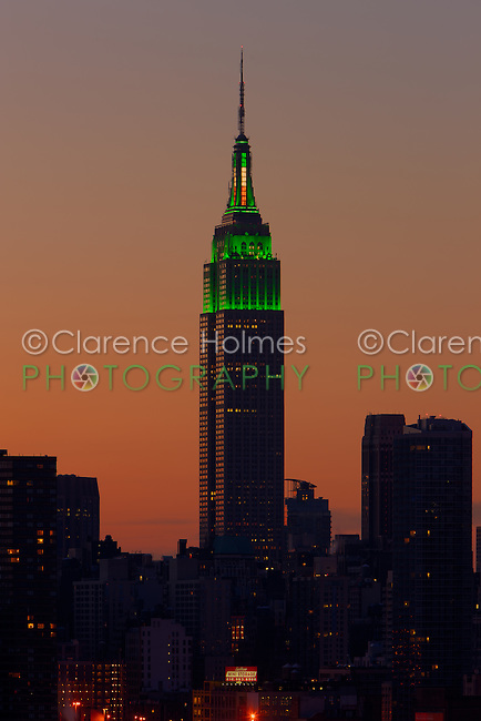 The Empire State Building, illuminated in green lights to celebrate St. Patrick's Day, contrasts with the orange glow of the pre-dawn sky on March 17, 2013 in New York City.