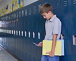 USA, Illinois, Metamora, Boy (10-11) standing at lockers in school corridor and text messaging