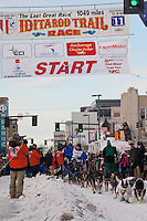Musher Judy Currier and  Iditarider Marty Vega.leave the 2011 Iditarod ceremonial start line in downtown Anchorage, Alaska