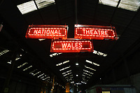 "Pictured: A National Theatre Wales nenon sign by the entrance to the industrial unit<br /> Re: Press rehearsal of ""We'Re Still Here"", a play created by Rachel Trezise, Common Wealth and the National Theatre Wales about steelworkers, which will be performed in Byass Works, a disused industrial unit, in Port Talbot, south Wales, UK."
