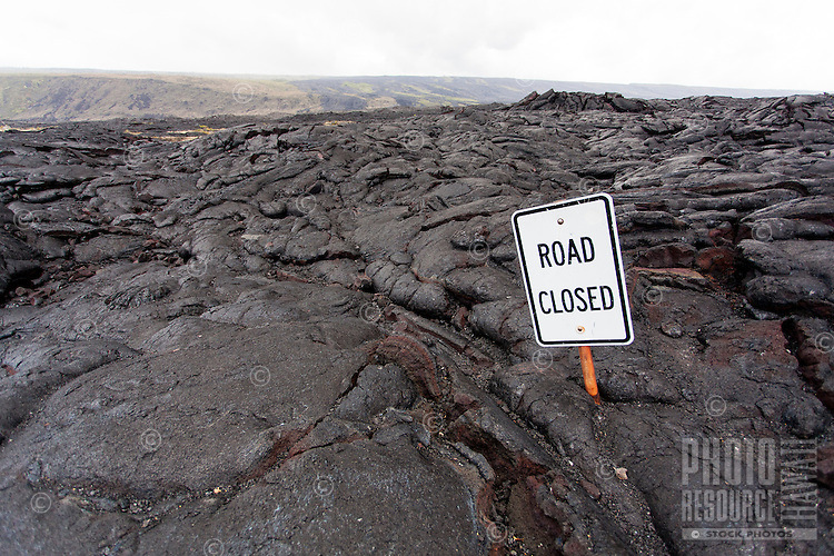 """""""Road Closed"""" sign emerging from lava field, Hawai'i Volcanoes National Park, Big Island."""