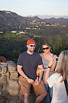 A couple has their picture taken with the Hollywood Sign in the background from a viewpoint on Mulholland Drive, Los Angeles, CA