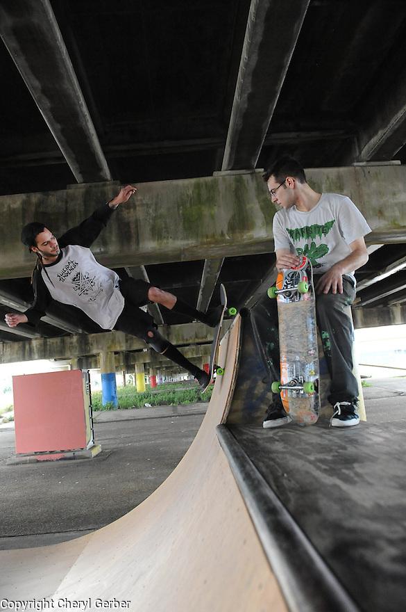 Makeshift skateboard park under interstate..