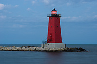 A summer evening view of the vibrant red Manistique Lighthouse and its red light beacon along the shores of Lake Michigan. Manistique, MI