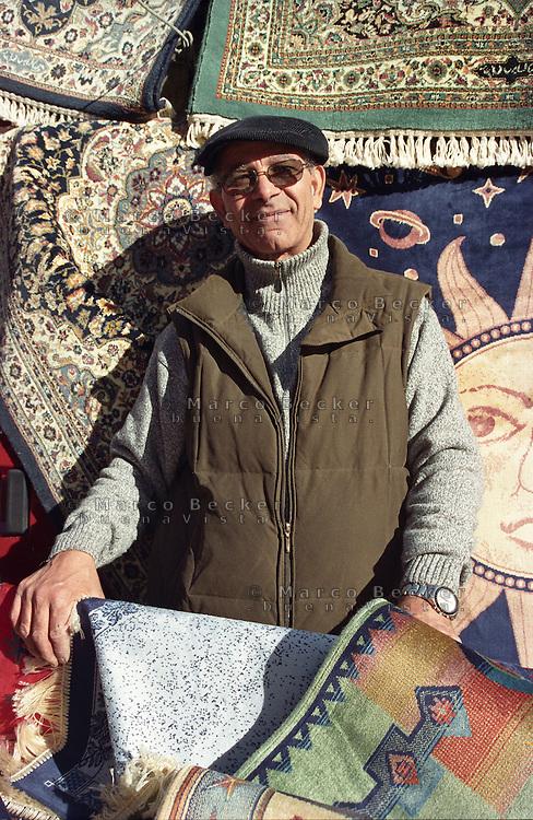 Milano, mercato rionale di viale Papiniano. Venditore di tappeti --- Milan, local market in Papiniano street. Carpet vendor