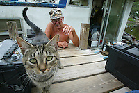 """Lifelong resident on the St. Johns River Stanley Oglesby, 70, visits a cat who adopted him on his houseboat at Rod and Siivi's Fish Camp in Geneva, Florida Thursday May 15, 2003. Oglesby, who lives at the camp on his houseboat, was born on the river and has stayed his entire life living on the river, saying, """"the river is the only way of life for me, I don't want to live anywhere else"""".(Kelly Jordan)"""